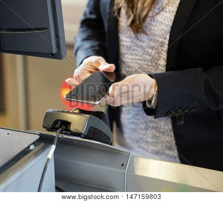 Customer Doing NFC Payment At Checkout Counter