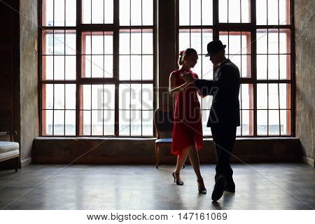 Woman in dress and man in black suit dance tango near big window in room