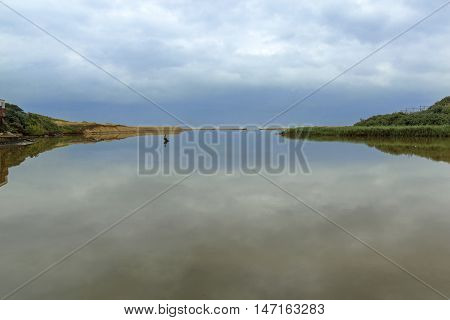Gloomy overcast sky and coastal vegetation reflections on water at river mouth lagoon