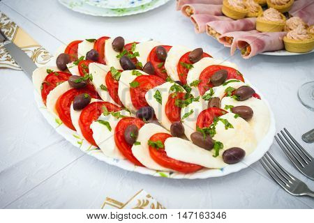 Cocktail food appetizer with slices of mozzarella tomatoes and olives