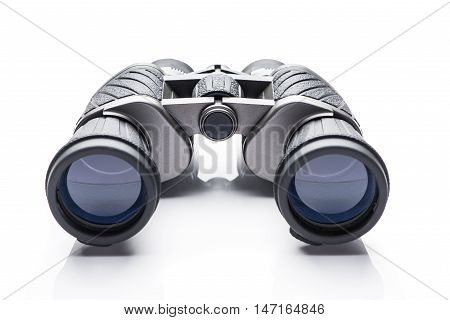Black modern binoculars over white background. A pair of binoculars on a white background.