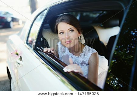 Beauty bride in bridal gown with lace veil in the car. Beautiful model girl in a white wedding dress. Female portrait in the auto. Woman with hairstyle. Cute lady outdoors