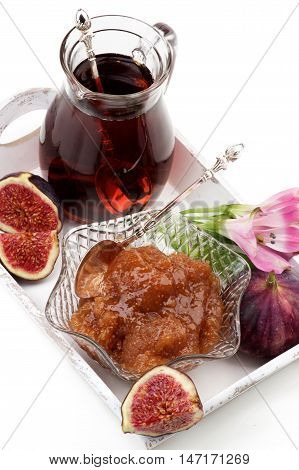 Arrangement of Delicious Homemade Fig Jam in Glass Kremanka with Fresh Fig Fruits Flowers and Jag of Fruit Drink in White Wooden Tray closeup on White background