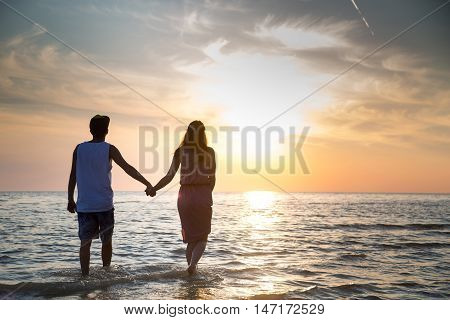 A Young Couple In Love Walks On The Beach At Sunset Holding Hands. The Concept Of Love And Affection