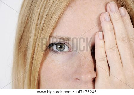 Close up portrait of a young woman with sun spotted face. She is covering one of her eyes with her hand. Studio shot with isolated light background.