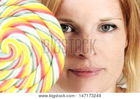 Nice funny woman is holding a huge colorful lollipop. Studio shot with isolated light background.