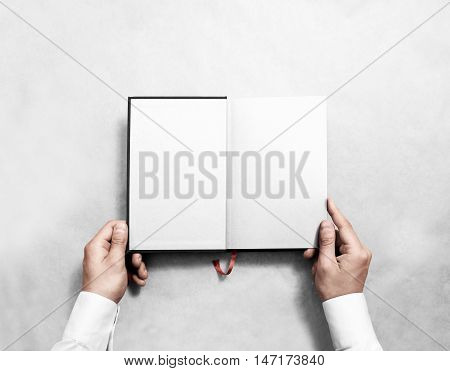 Hand holding blank opened book mock up with white half title. Person reading empty paperback mockup. Black notebook inside template. Publication design leafing man. Textbook spread with bookmark.