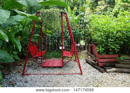 Red Swing Hanging In Garden