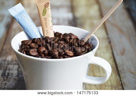 Kaffekop med hele bønner, samt sukker og fløde