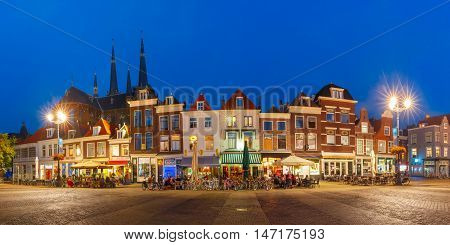 Panorama wiyh typical Dutch houses on the Markt square in the center of the old city at night, and Maria van Jessekerk on the background, Delft, Holland, Netherlands