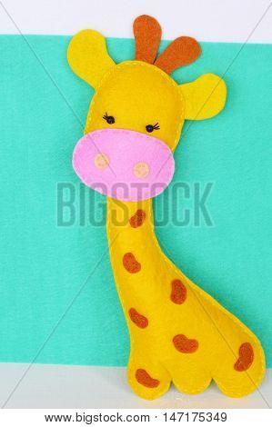 Funny yellow giraffe sewn from felt. Soft children's toy. Stuffed giraffe toy