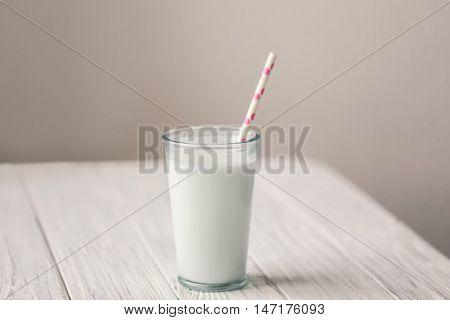 Glass of fresh milk on white wooden table
