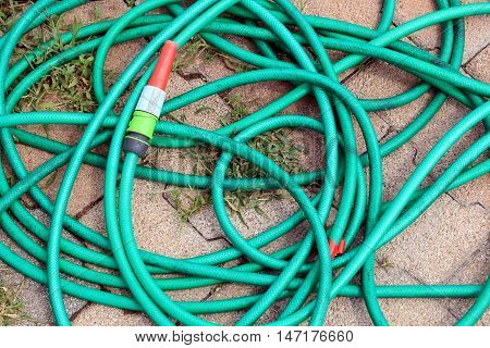 Green garden water hose with red and white nozzle coiled up untidily on a stone block background with weeds.