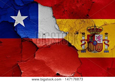 flags of Chile and Spain painted on cracked wall