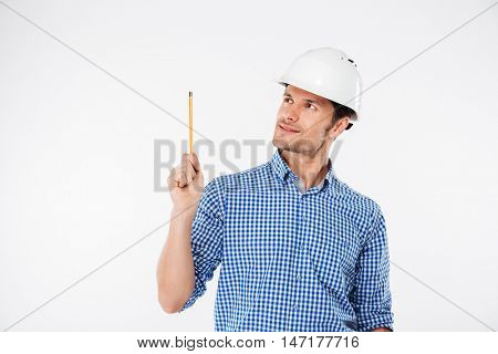 Cheerful young man building engeneer in hard hat pointing up with pencil