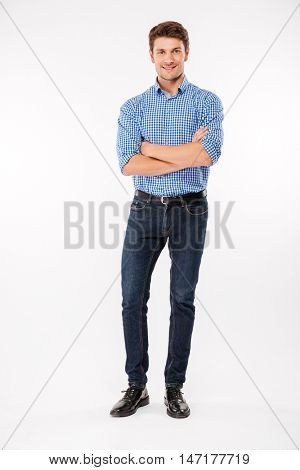Full length of happy attractive young man standing with arms crossed over white background