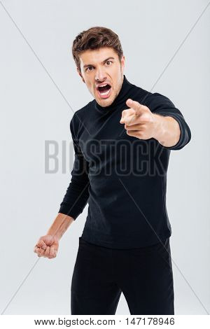 Angry furious young man shouting and pointing on you
