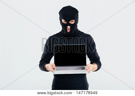 Criminal man in balaclava holding blank screen laptop