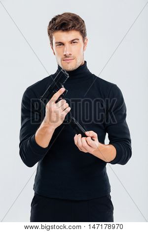 Serious young man standing and loading a gun