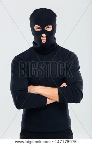 Portrait of man in balaclava standing with arms crossed