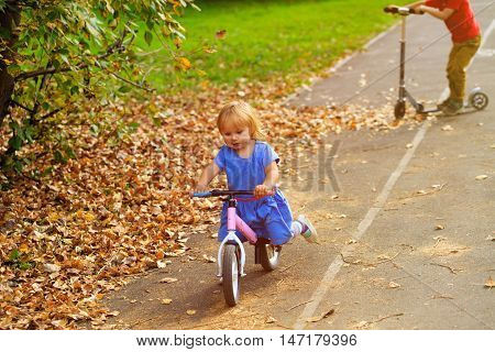 cute little girl riding runbike and boy riding scooter in autumn, active kids sport