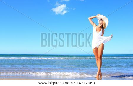 Young woman standing on a beach and enjoying the sun poster