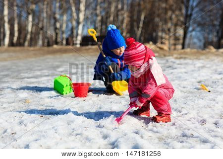 little boy and girl digging snow in winter, kids winter activities