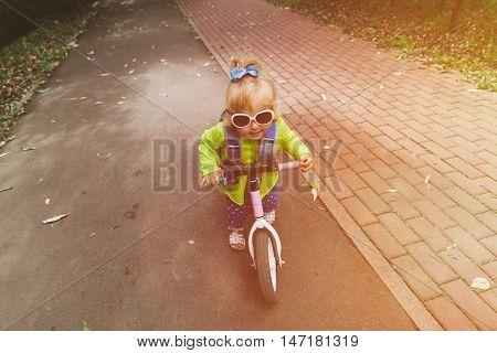 little girl riding runbike outdoors, active kids sport
