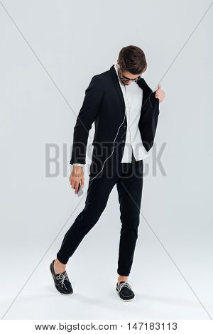 Full length portrait of a happy attrative young businessman in black suit listening music with earphones and dancing over gray background