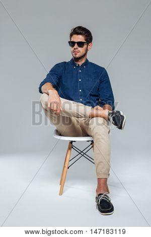Handsome relaxed man in suglasses sitting on the chair over gray background