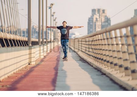 Skateboarder Skates Over A City Bridge. Free Ride Street Skateboarding