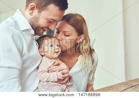 Smiling mother and father holding their newborn baby daughter at home