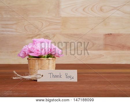 Handwriting Thank you on brown label and bouquet of Carnation flower with wood background