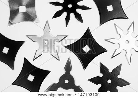 Different black and silver shurikens are on white background.