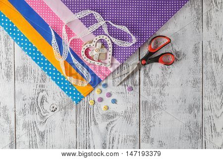 cotton fabrics for sewing lace and accessories for needlework on wooden background. Set for needlework top view poster
