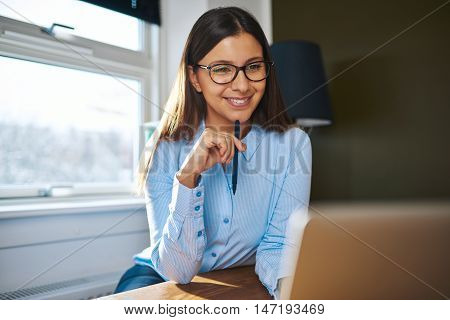 Positive young female self-employed business owner in eyeglasses and long brown hair with pen near chin working on laptop