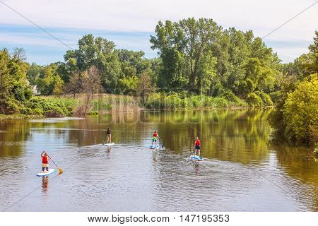 Group of people Paddleboarding on a river at sunrise