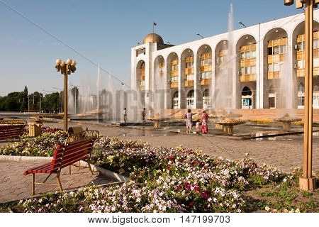 BISHKEK, KYRGYZSTAN - JULY 31, 2013: People walking around fountains at the country's main square Ala-Too on July 31, 2013 Kyrgyzstan. Kyrgyzstan's population is 5.2 mill 34.4 perc. are under age 15