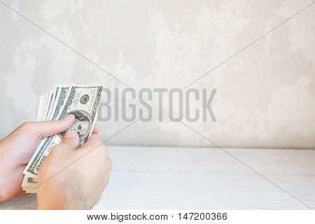 Hand with batch of one hundred dollars, free space. Man counting american money, white background. Currency exchange, profit. win gambling concept