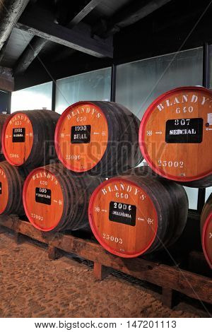 FUNCHAL, MADEIRA - OCTOBER 08, 2011: Museum - repository of expensive vintage wine Madera. Huge barrels labeled data of sweet wine