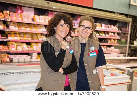 Team Of Smiling Happy Salespeople In A Supermarket