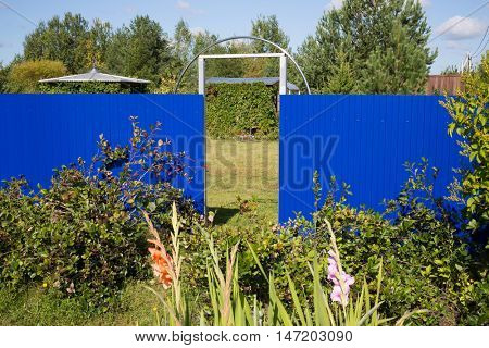 Beautiful landscape with a blue fence and passage between the neighboring houses