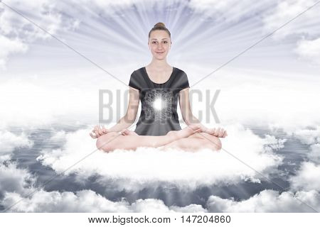 Smiling girl in yoga lotus position on the clouds that form a circle around her in front of her a ball of energy that emits rays at the bottom a blue sky from which come other light rays