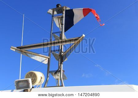 Navigational and safety equipment on a Mediterranean boat flying the French Tricoleur flag against a clear blue sky