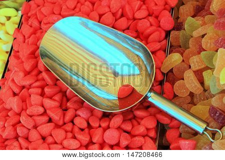 Tray of red candy sweets with stainless steel scoop