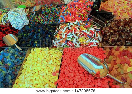 Trays of colorful candy sweets red blue yellow and multi-coloured with stainless steel scoops