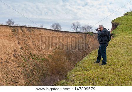Mature photographer taking photo standing on the edge of ravine at spring season