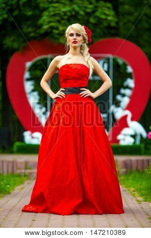 portrait of beautiful woman in red dress in summer park standing before wedding installation