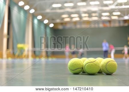 some tennis balls on tennis court in sports hall, blurred background