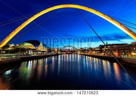 Newcastle and Gateshead at sundown showing Gateshead Millennium Bridge sage and Tyne Bridges.